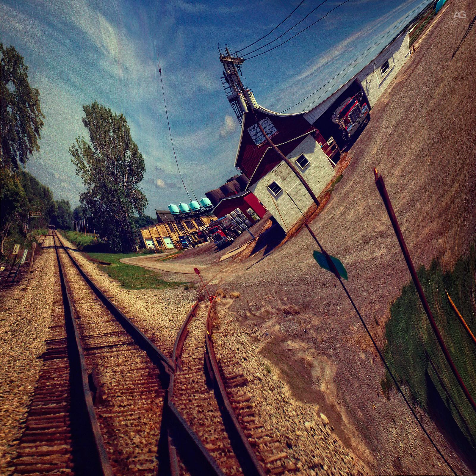 TrainTracksAndWhiteSmallHouseCloudyDayMiddleOfNowhere_warped_1600