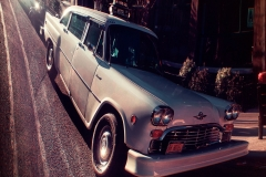 WhiteVintageCarTaxiOnTheStreetsOfGreenPoint_warped_1600